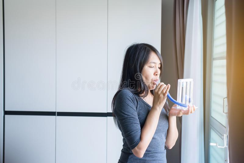 El paciente que usa incentivespirometer o tres bolas para estimula el pulmón imagen de archivo libre de regalías