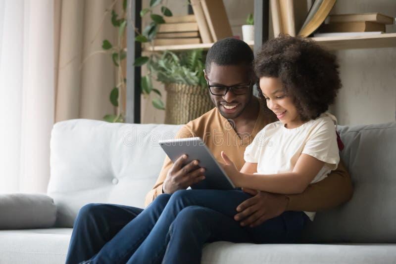 El padre africano se sostiene en la hija del revestimiento que tiene tableta del uso de la diversión imagenes de archivo