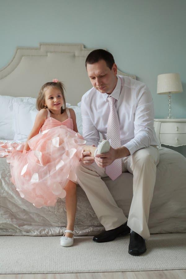 El padre ayuda a poner los zapatos su hija foto de archivo