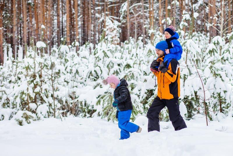 El padre camina con sus niños jovenes en el bosque en invierno imágenes de archivo libres de regalías