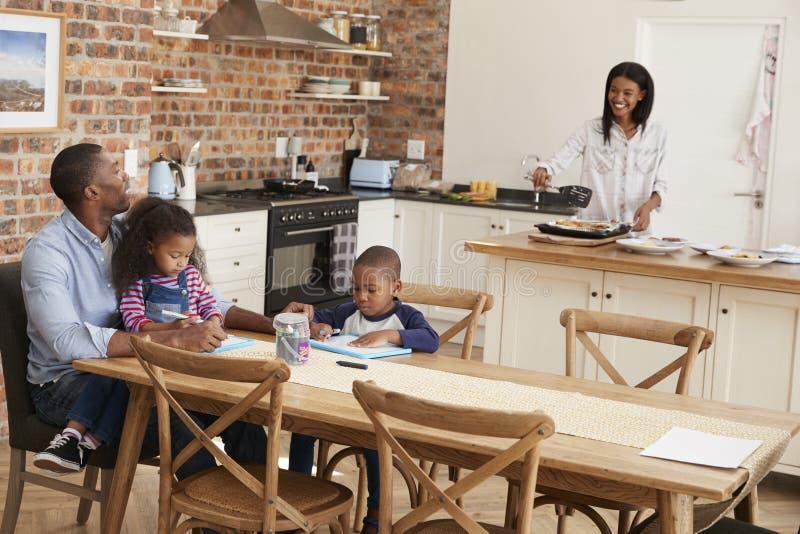 El padre And Children Drawing en la tabla como madre prepara la comida fotos de archivo libres de regalías