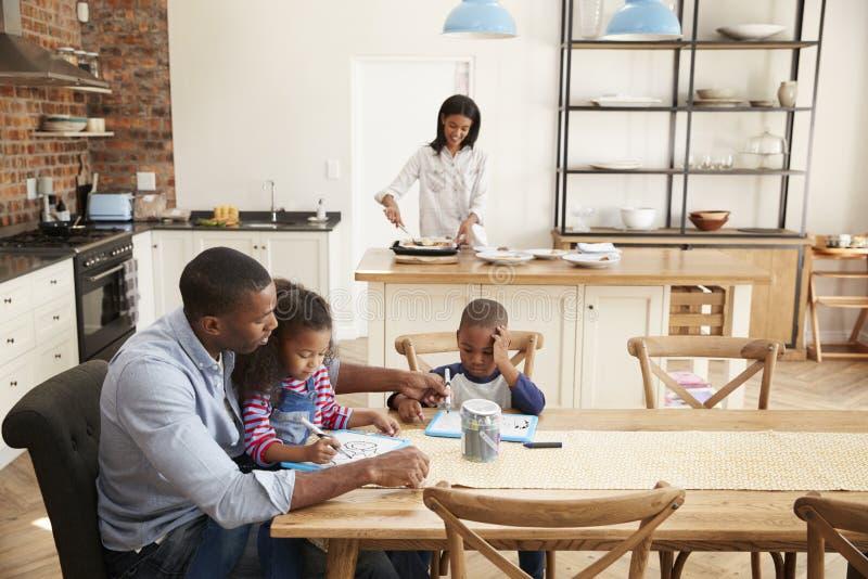 El padre And Children Drawing en la tabla como madre prepara la comida imagen de archivo libre de regalías