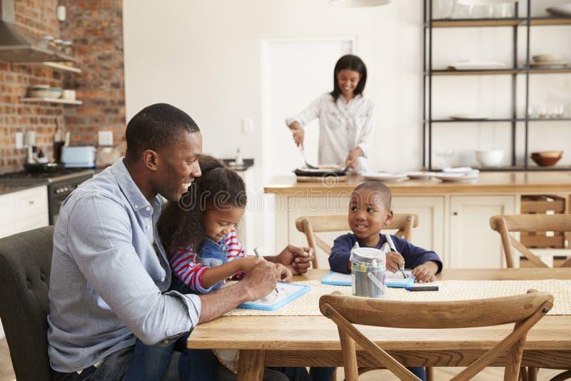 El padre And Children Drawing en la tabla como madre prepara la comida fotografía de archivo