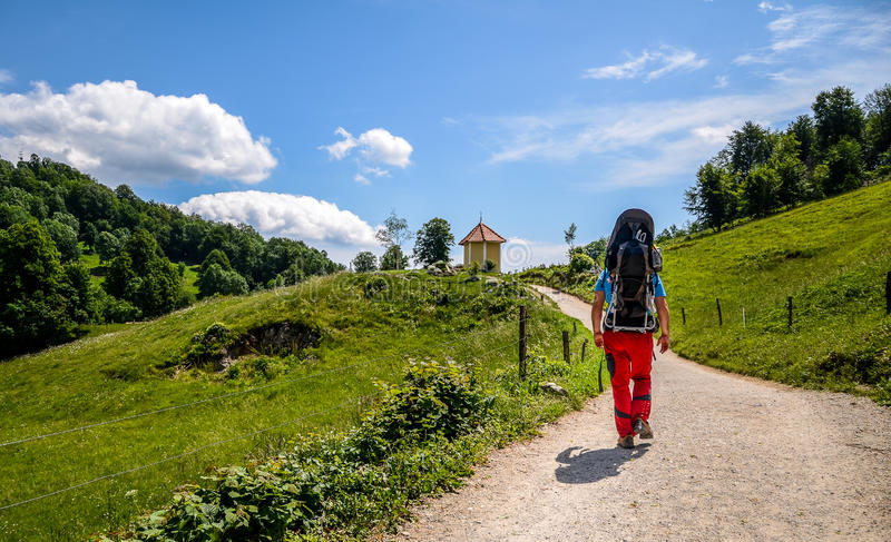 El padre con el bebé en portador de la mochila está caminando en montañas fotos de archivo