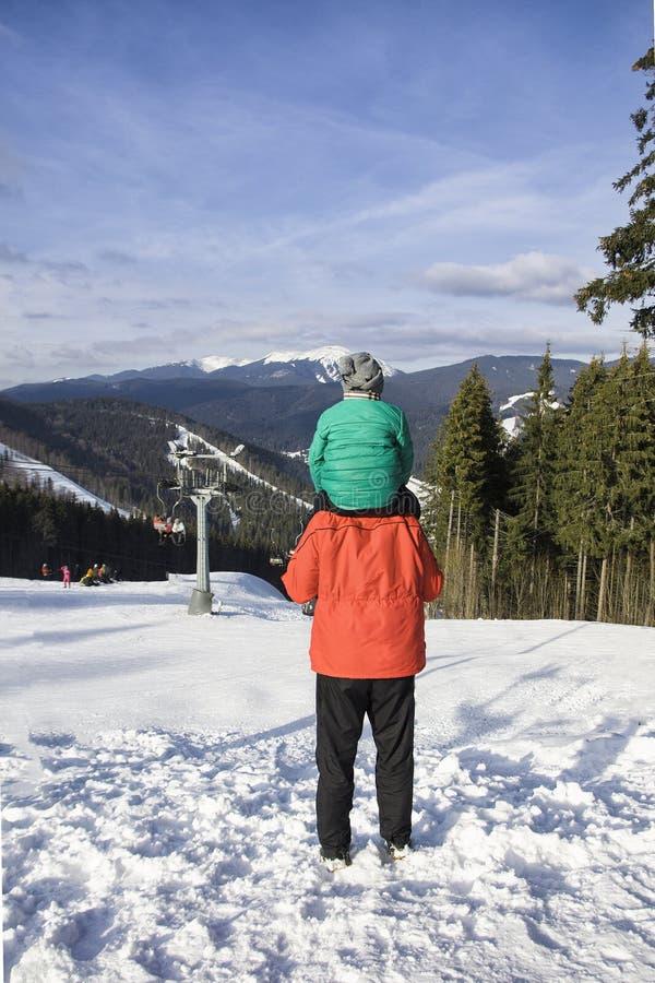 El padre con el hijo en hombros se opone al contexto de montañas, de la elevación del cable y del día de invierno conífero del bo fotografía de archivo libre de regalías