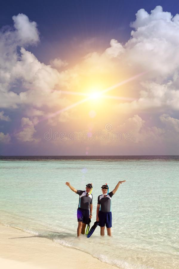 El padre con el hijo en el mar con el equipo para bucear fotos de archivo