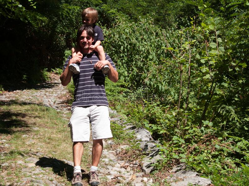 El padre con el hijo en sus hombros viene abajo de una trayectoria de bosque o foto de archivo libre de regalías