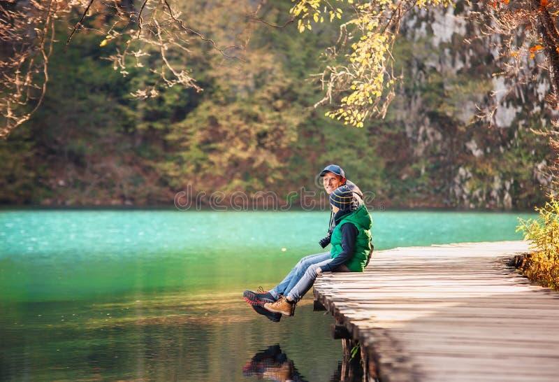 El padre con el hijo se sienta en el puente cerca del lago de la montaña, naturaleza nacional imagen de archivo libre de regalías