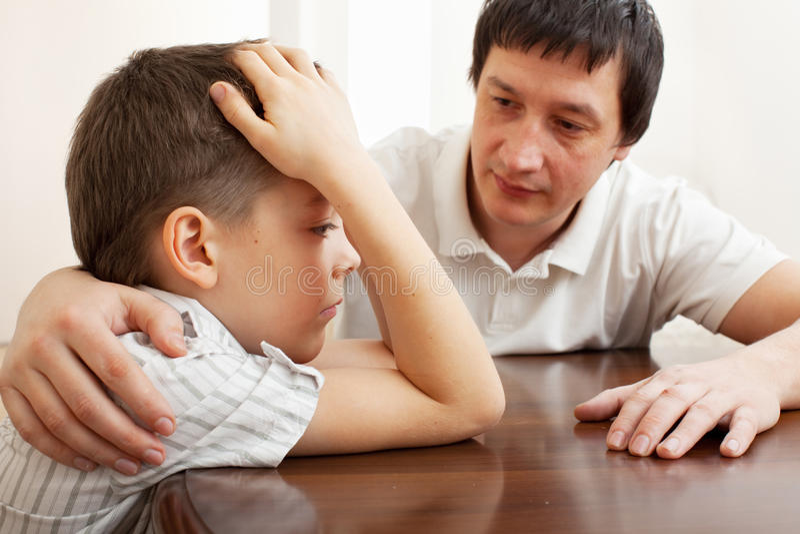 El padre conforta a un niño triste