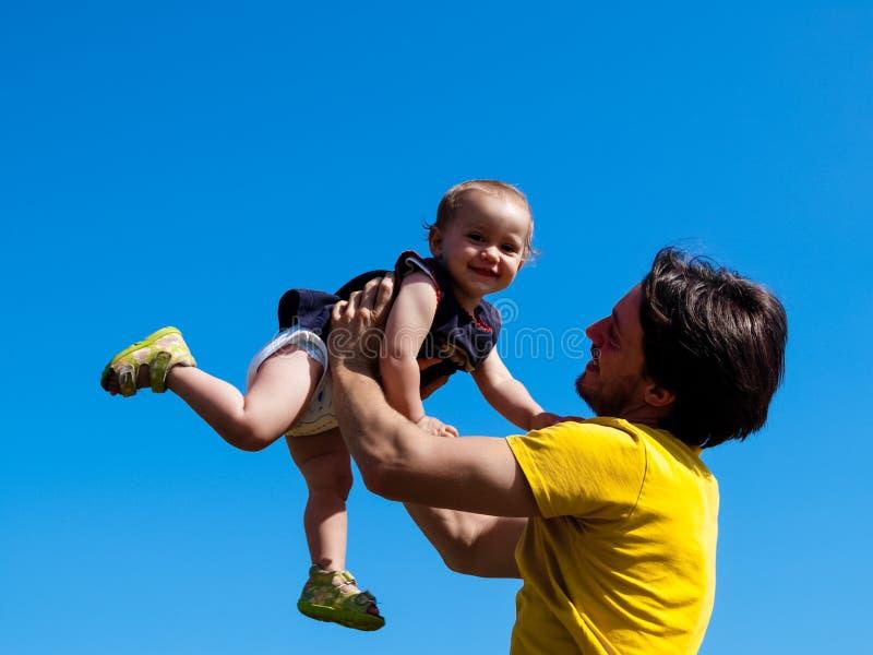 El padre cría para arriba a su pequeña hija y ella ríe feliz fotos de archivo