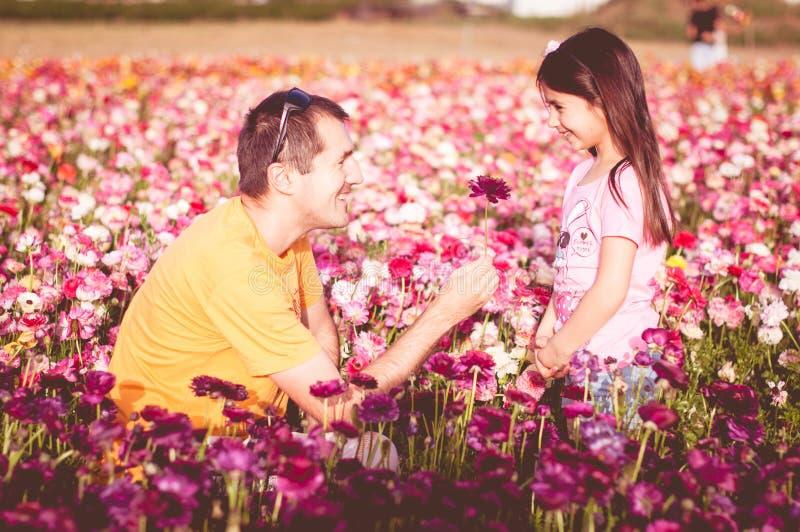 El padre da a su hija una flor imagen de archivo libre de regalías