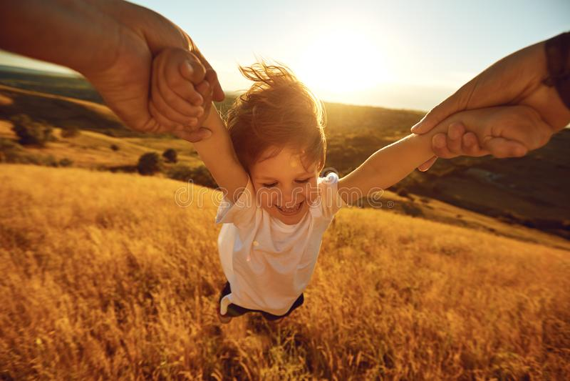 El padre da vuelta a un niño en el campo en naturaleza foto de archivo