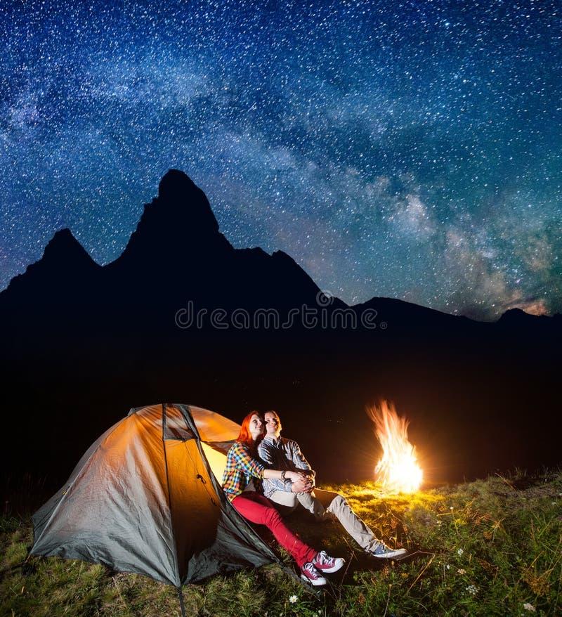 El padre de familia turístico y la mujer que miran a brilla el cielo y la vía láctea estrellados en acampar en la noche cerca de  imagenes de archivo