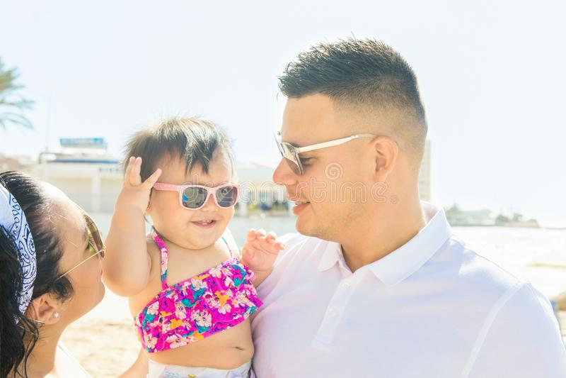 El padre del hombre joven detiene a su pequeña muchacha linda de la hija del bebé en la mujer joven de la madre de las manos que  imagenes de archivo