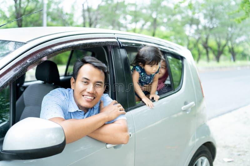 El padre del retrato cruzó las manos en la ventanilla del coche cuando mirada en la cámara fotos de archivo