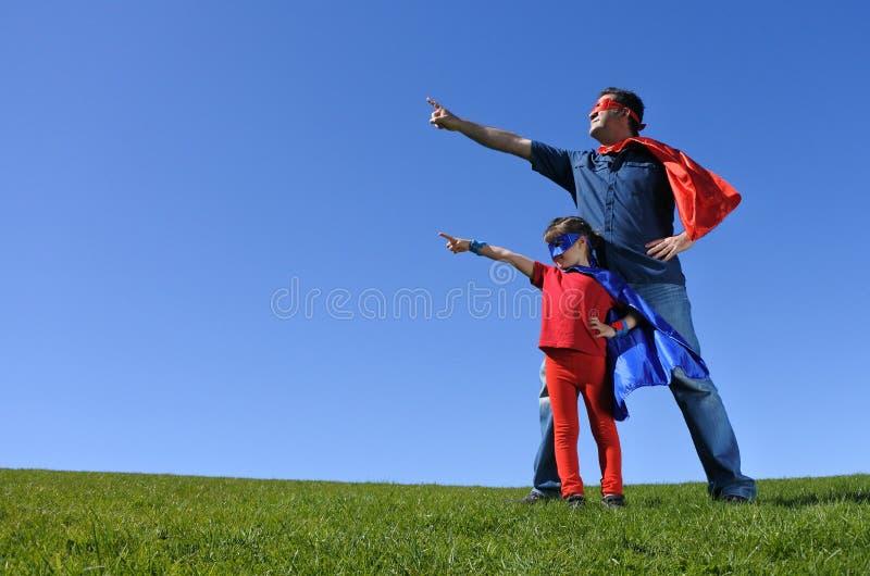 El padre del super héroe muestra a su hija cómo ser un super héroe imagen de archivo