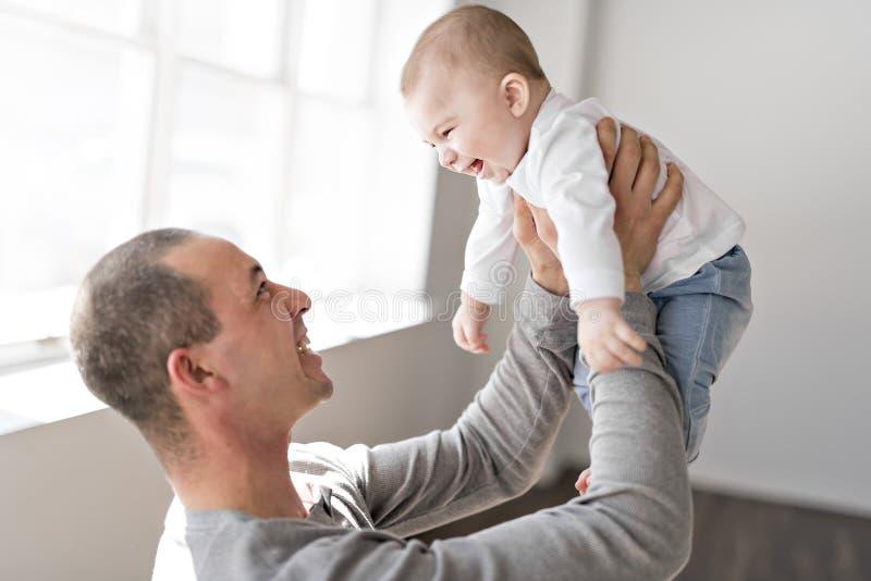 El padre detiene al bebé en un cuarto hermoso con las ventanas blancas imágenes de archivo libres de regalías