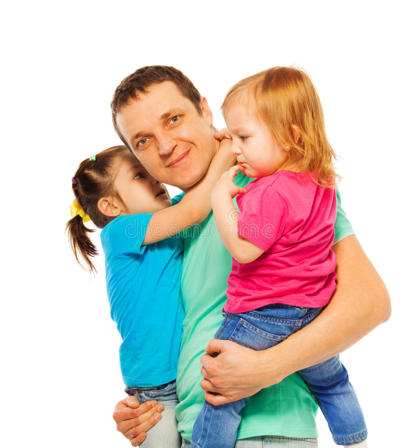 El padre detiene a dos hijas en sus brazos fotos de archivo