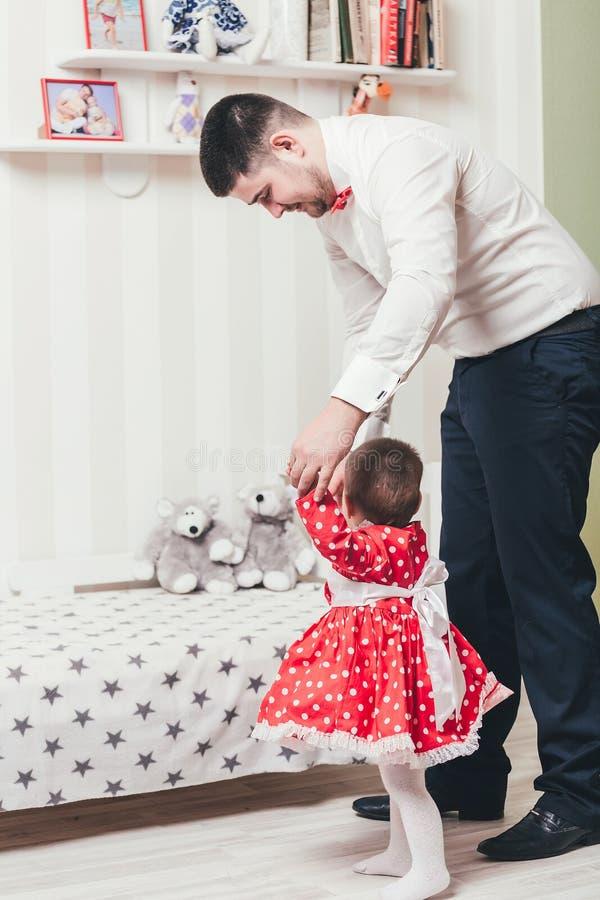 El padre detiene a una hija de un año al lado de la mano y le ayuda a ir El papá y la pequeña hija están jugando en el cuarto fotografía de archivo