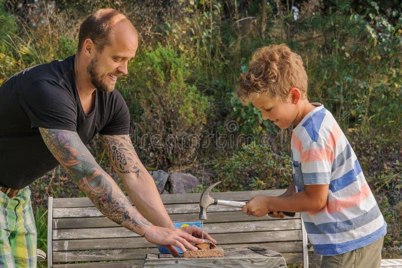 El padre enseña hijo a cómo utilizar un martillo foto de archivo
