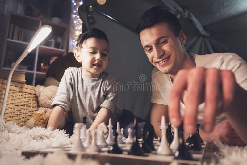 El padre enseña pequeño hijo a cómo jugar a ajedrez en la noche en casa imagen de archivo