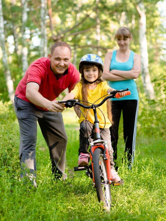 El padre enseña a su hija a montar una bici fotos de archivo libres de regalías