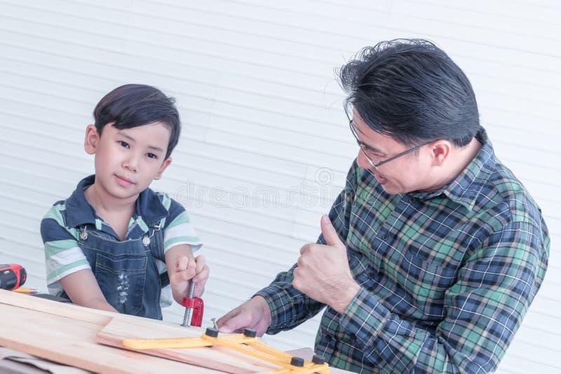 El padre está enseñando a su muchacho a trabajar en las herramientas de la artesanía en madera de la construcción fotos de archivo libres de regalías