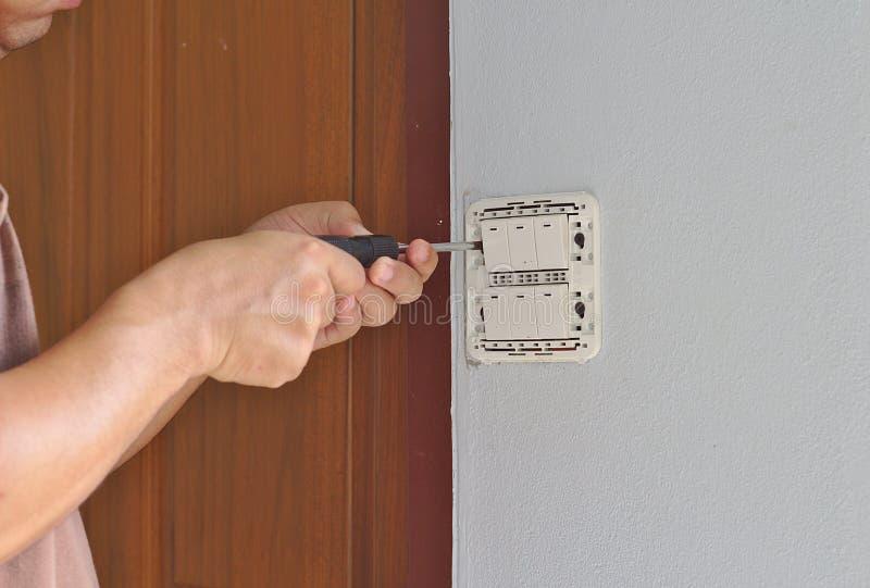 El padre está reparando el panel del interruptor en el cuarto en la pared con un destornillador fotografía de archivo libre de regalías