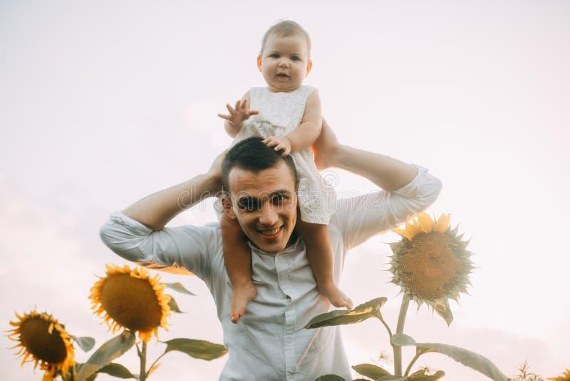 El padre feliz con su pequeña hija está en el campo del girasol foto de archivo
