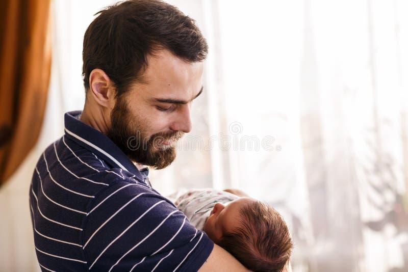 El padre feliz detiene a su bebé durmiente recién nacido imágenes de archivo libres de regalías