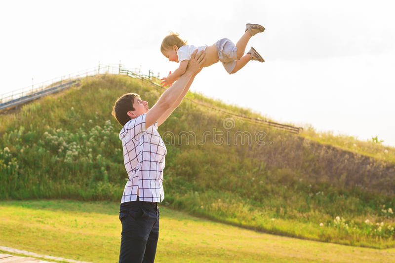 El padre feliz joven que detiene al hijo del bebé adentro entrega su cabeza al aire libre imagenes de archivo