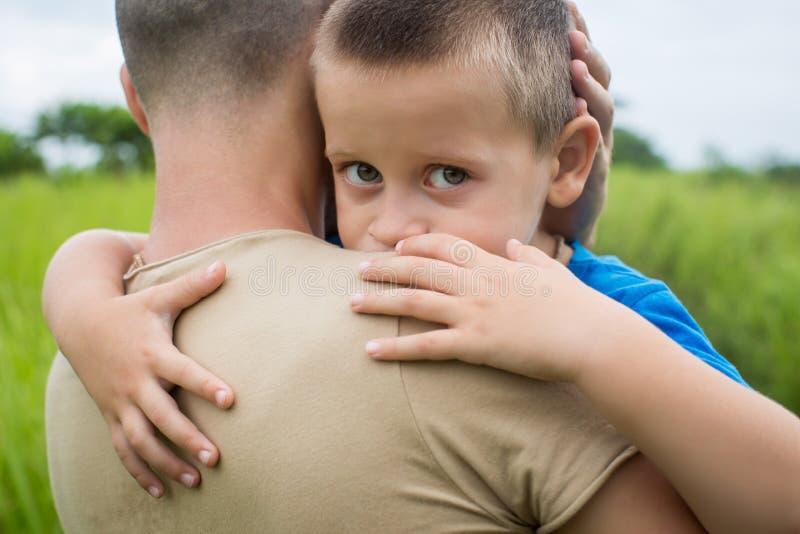 El padre feliz joven que soporta en el suyo arma al pequeño hijo imagen de archivo