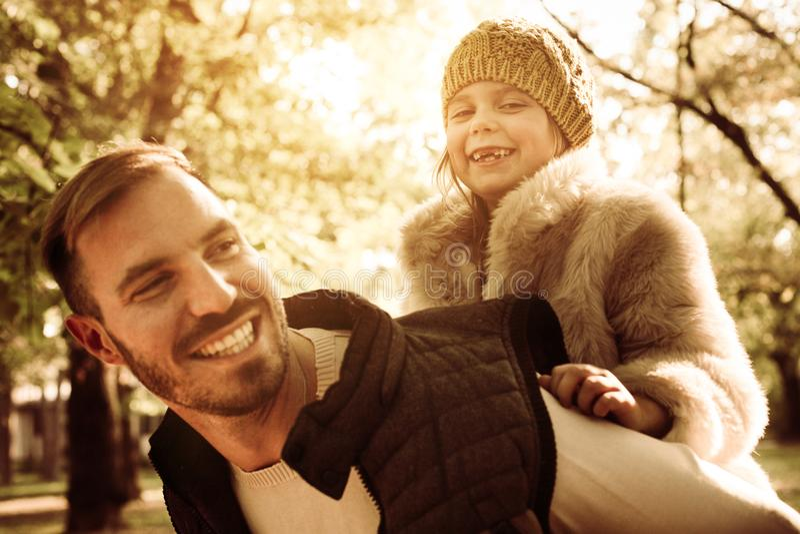 El padre feliz que lleva a su hija encendido me lleva a cuestas parquea foto de archivo