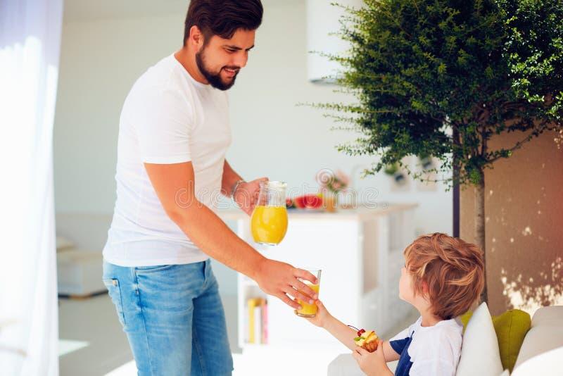 El padre feliz trata al hijo con el jugo fresco y el postre sabroso en el jardín del patio del verano imágenes de archivo libres de regalías