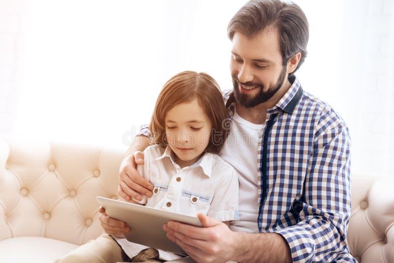 El padre feliz y el hijo joven están mirando la tableta del ordenador foto de archivo