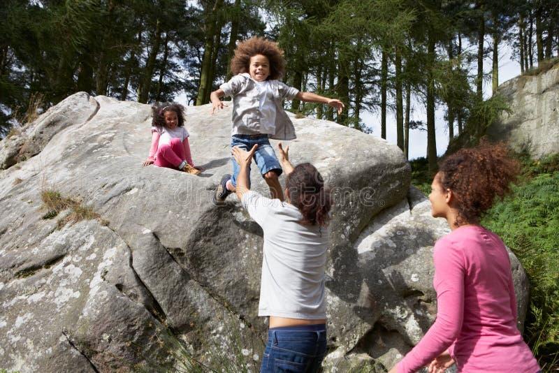 El padre Helping Children To salta de rocas imágenes de archivo libres de regalías