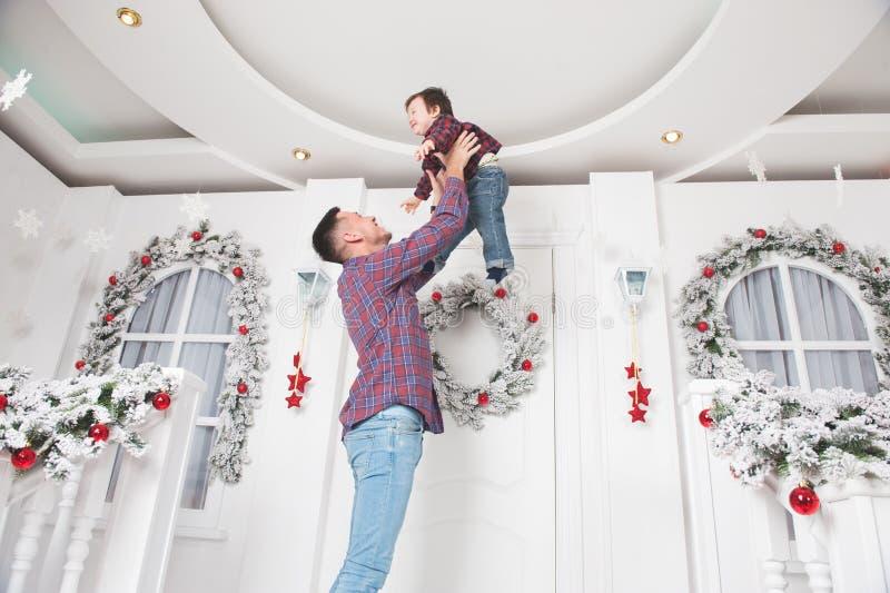 El padre joven caucásico feliz lanza a poco hijo para arriba en nueva y feliz fotografía de archivo libre de regalías