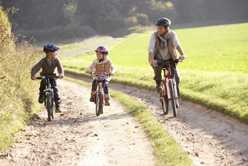 El padre joven con los niños monta las bicis en parque fotos de archivo libres de regalías