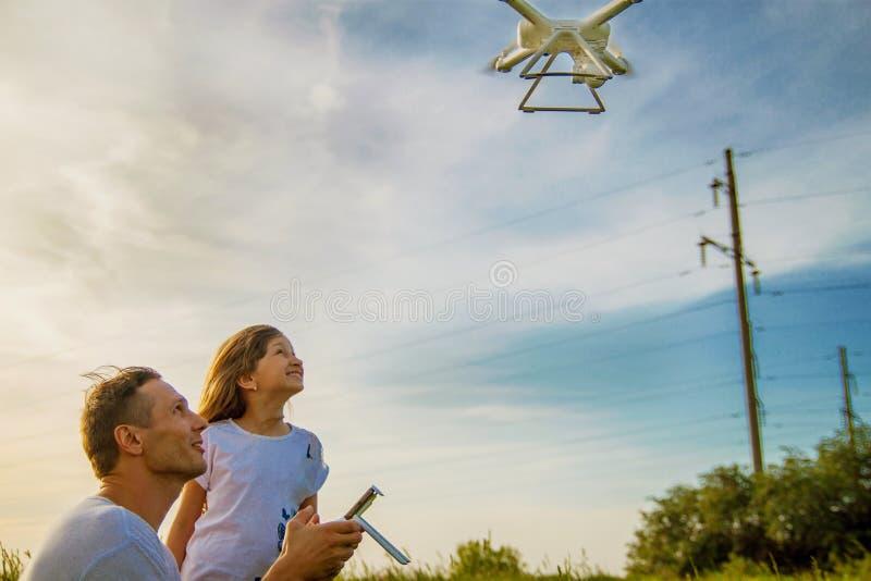 El padre joven muestra a su hija linda cómo controlar el abejón al aire libre fotos de archivo libres de regalías