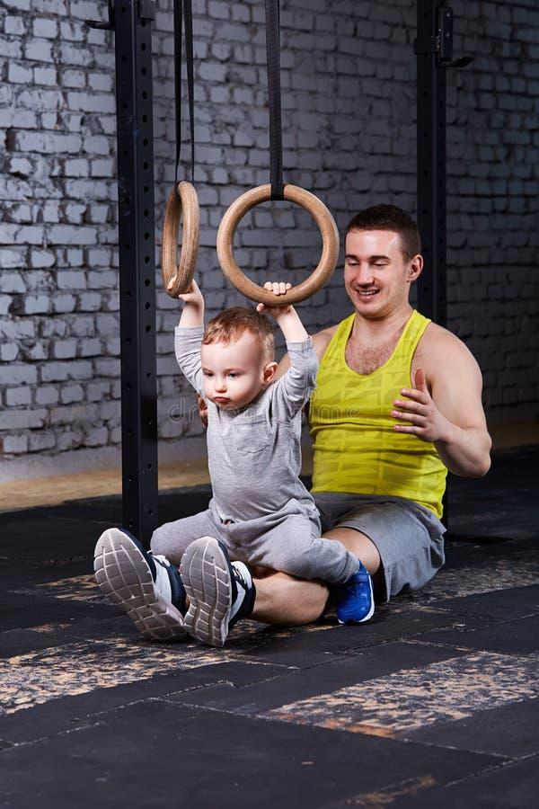 El padre joven sonriente entrena al pequeño hijo con los anillos gimnastic contra la pared de ladrillo en el gimnasio fotos de archivo libres de regalías