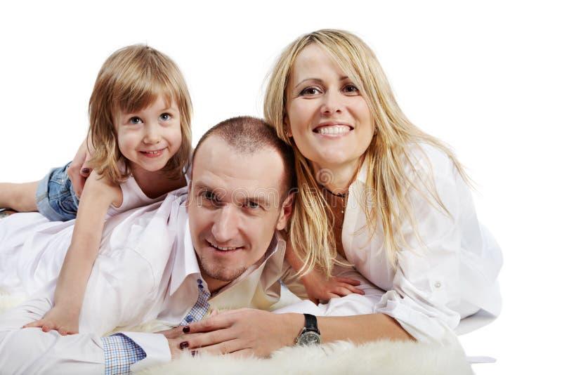 El padre, la madre y la hija mienten en la alfombra imagenes de archivo