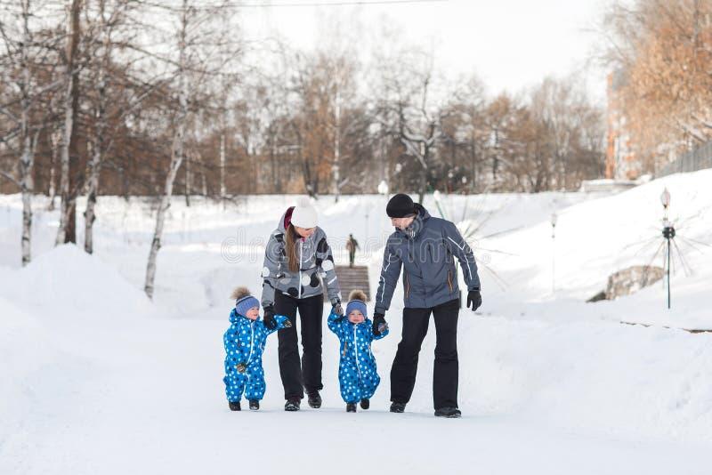 El padre, la madre y los niños, gemelos se detienen las manos y el caminar en la nieve fotos de archivo