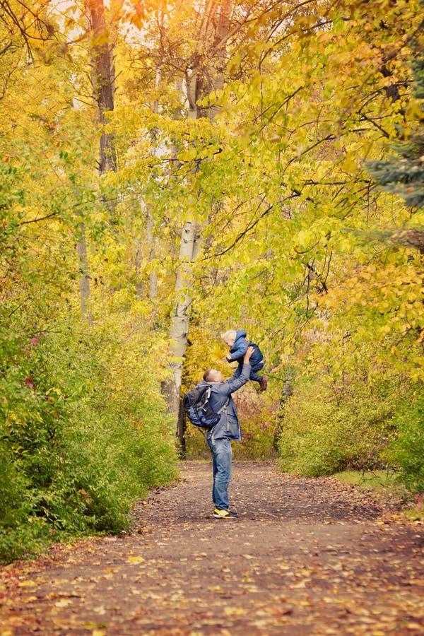 El padre lanza a un pequeño hijo Parque del otoño Vista lateral imagenes de archivo