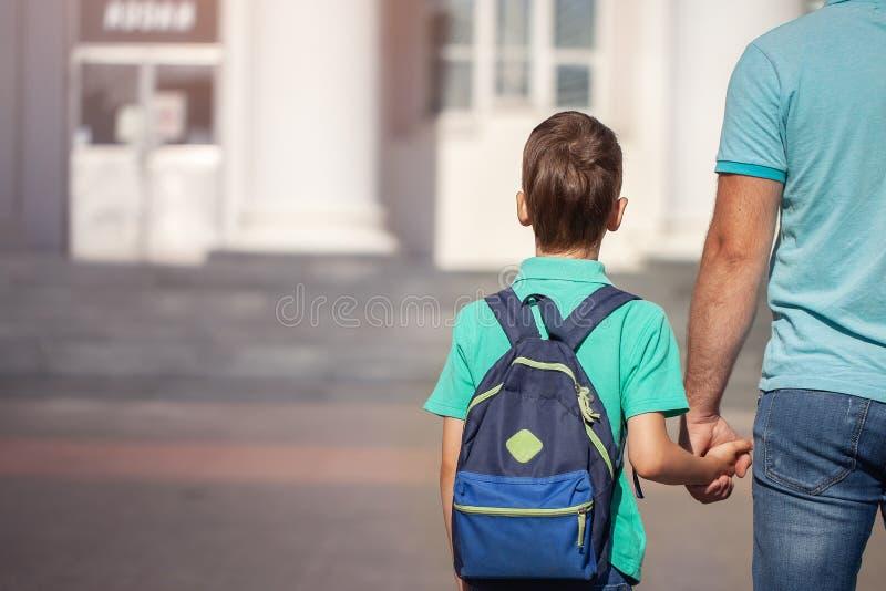El padre lleva a un pequeño niño que va el escolar de común acuerdo Padre e hijo con la mochila detrás de la parte posterior fotografía de archivo libre de regalías