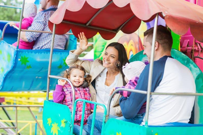 El padre, madre, hijas que disfrutan de la feria de diversión monta, parque de atracciones fotografía de archivo libre de regalías