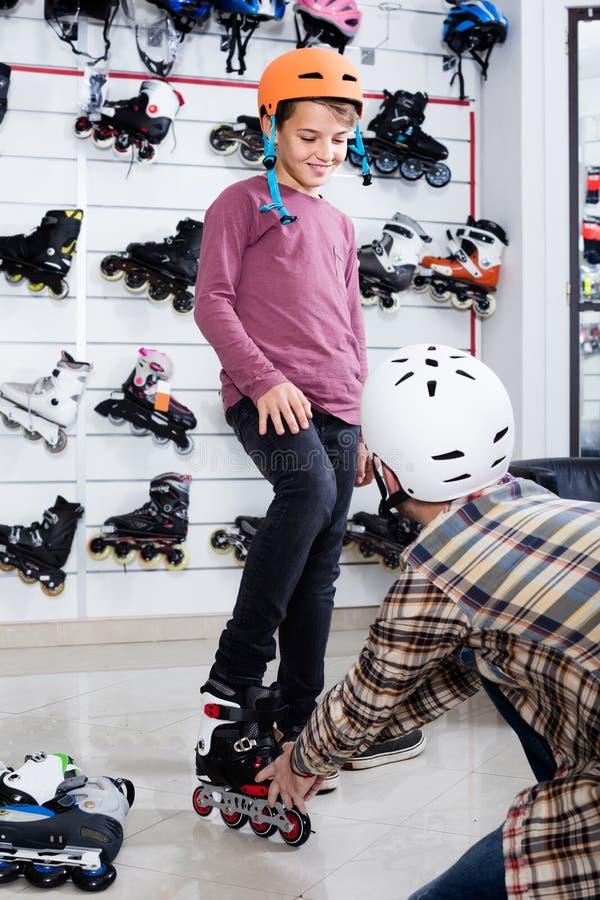 El padre que ayuda al hijo en intentar encendido patina sobre ruedas en tienda de los deportes imagenes de archivo