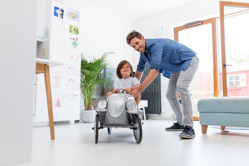 El padre que ayuda a su hijo a conducir un juguete vende puerta a puerta el coche imágenes de archivo libres de regalías
