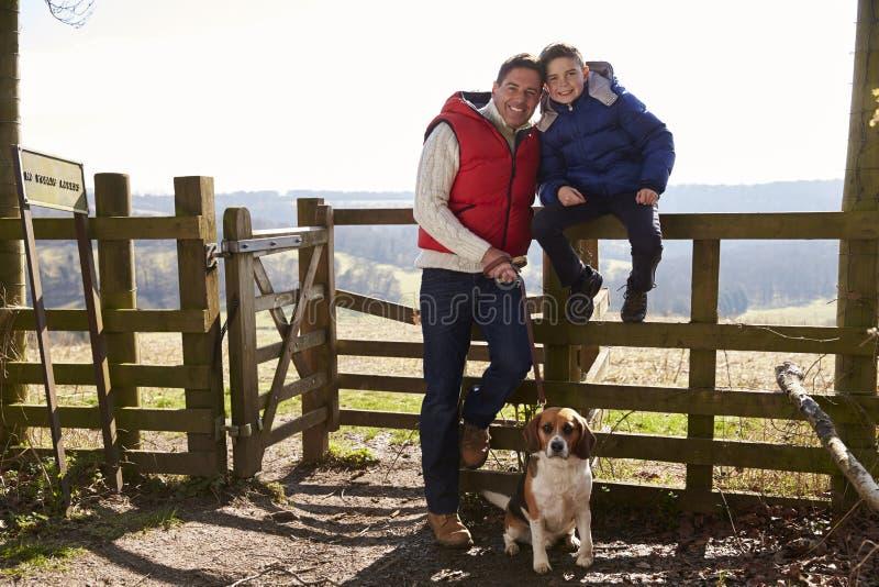 El padre se coloca con el perro, hijo que se sienta en una cerca rural imagen de archivo