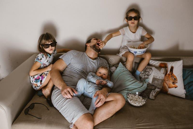 El padre se está sentando en el sofá con el bebé en sus brazos y sus dos hijas en los vidrios especiales que miran la TV y la con imagenes de archivo