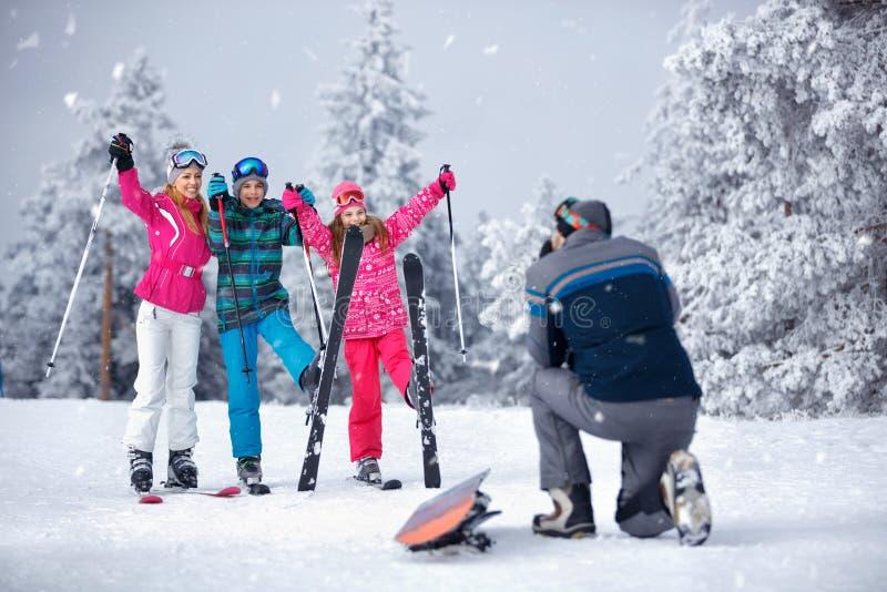 El padre toma la fotografía de la familia el vacaciones del invierno en moun de la nieve fotografía de archivo libre de regalías